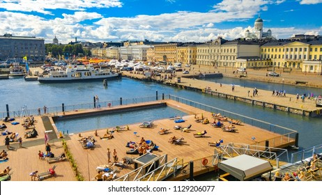 Helsinki, Finland 7.7.2018 Allas Sea Pool, Market Square, Presidental Palace and behind Helsinki Lutherdal Catetral . Suomenlinna ferry has just arrived at the beach. Sunny summer day in the capital