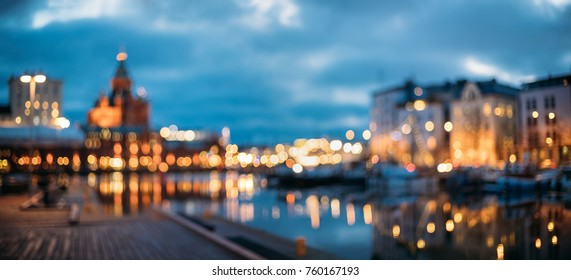 Helsinki, Finland. Abstract Blurred Bokeh Architectural Urban Panoramic Background Of Uspenski Cathedral And City Embankment. Defocused Backdrop Lights Of City Street In Evening Night Illumination