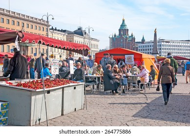HELSINKI, FINLAND - APRIL 16, 2011:  People in the open air cafe on the Market Square near Gulf of Finland. On the background is Uspenski Cathedral