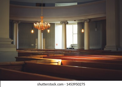 Helsinki, Finland - April 30, 2018: Interior of Helsinki Cathedral. Church pews, pillars, vintage golden chandelier, architectural details and decorations. Finnish Evangelical Lutheran cathedral.