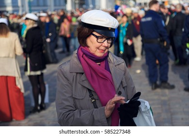 HELSINKI, FINLAND - APRIL 30,2015. May Day Labor day celebration in Helsinki. Woman wearing white cap and sending text message on a mobile phone. Vappu