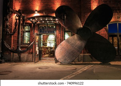 HELSINKI, FINLAND - AUGUST 10th 2017:  Old brick seaport storage houses re-purposed for bars and restaurants with anchor and huge propeller at entrance at night