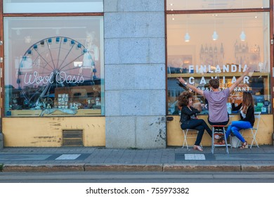 HELSINKI, FINLAND - AUGUST 10th 2017: Young people sitting in the evening in front of the bar drinking and talking with the image of the Helsinki ferris wheel reflecting in the window.