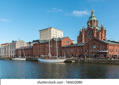 HELSINKI, FINLAND - AUGUST 10th 2017: Uspenski orthodox cathedral rising above the old brick seaport  storage houses re-purposed for bars and restaurants