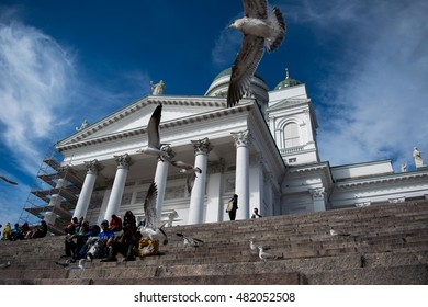 HELSINKI, FINLAND - AUGUST 19, 2016: Group of tourists sits on the stairs in front of Helsinki Cathedral.