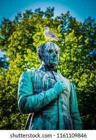 HELSINKI, FINLAND - August 19, 2018: A seagull sits on the head of the Johan Ludvig Runeberg statue in the Esplanade in Helsinki.