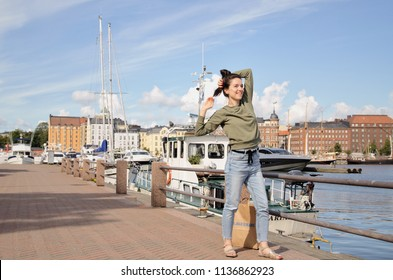 Helsinki, Finland, August 2017: Happy tourist girl standing outdoors in center city. Female smiling on Finnish embankment with yachts and boats, old buildings background. Urban. Editorial use only.