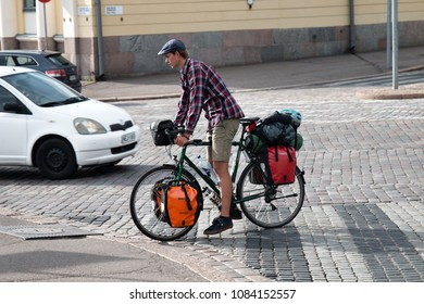 HELSINKI, FINLAND - AUGUST 22, 2017: Cyclist in town with front and rear Bicycle backpacks. Cyclist traveler