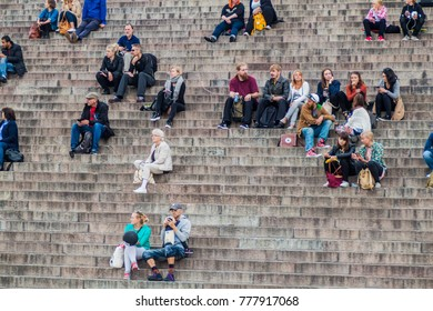 HELSINKI, FINLAND - AUGUST 25, 2016: People sit on stairs on the Senate Square in front of the Finnish Evangelical Lutheran cathedral.