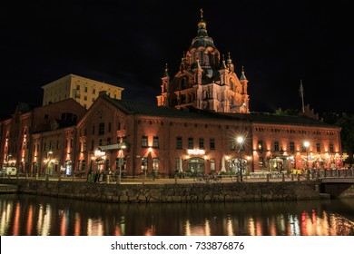 HELSINKI, FINLAND - AUGUST 9th 2017: Uspenski orthodox cathedral rising above the old brick seaport  storage houses re-purposed for bars and restaurants