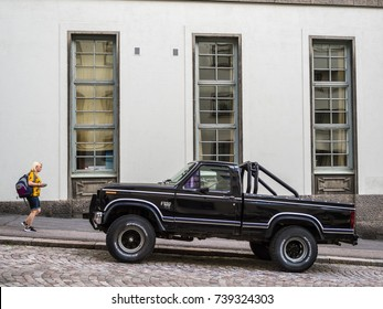 HELSINKI, FINLAND - AUGUST 9th 2017:  The person passing the big 4x4 pickup truck standing on the street in Helsinki on a sunny summer day.