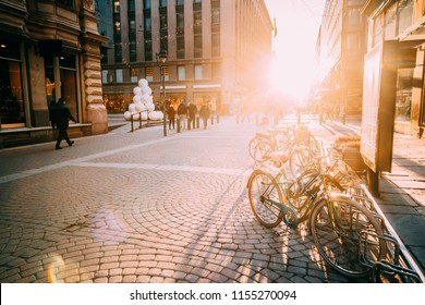 Helsinki, Finland. Bicycles Parked Near Storefronts In Kluuvikatu Street. View Of Street In Sunlight Decorated For Christmas And New Year Holiday.