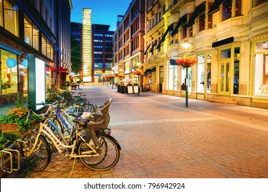 Helsinki, Finland. Bicycles Parked Near Storefronts In Kluuvikatu Street. Night View Of Kluuvikatu Street In Kluuvi District In Evening Or Night Illumination.