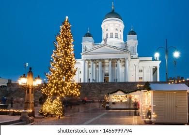 Helsinki, Finland. Christmas Xmas Holiday Carousel On Senate Square Near Famous Landmark. Lutheran Cathedral At Winter Evening.