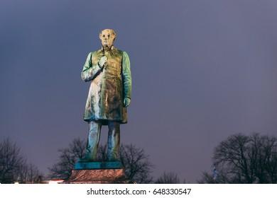 Helsinki, Finland. Close Up Of Statue Of Johan Ludvig Runeberg On Esplanadi Park In Lighting At Evening Or Night Illumination. Famous Landmark. Monument To National Poet And Lyric Of Finland.
