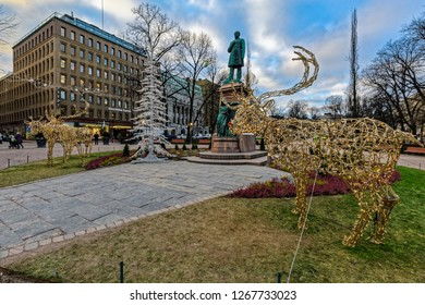HELSINKI, FINLAND - Dec 14, 2018: View to Esplanadi park during Christmas with statue of Johan Ludwig Runeberg in middle of the avenue and Christmas light deers figures at early morning.