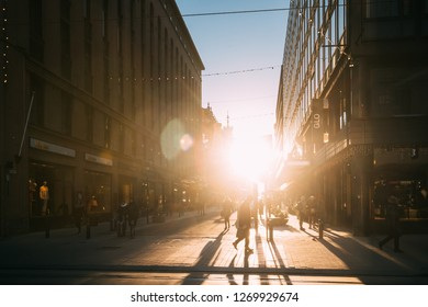 Helsinki, Finland - December 11, 2016: People Walking On Kluuvikatu Street In Winter Sunlight. Street Decorated For Christmas And New Year Holiday. Sunrise Morning Time