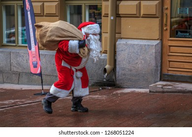 HELSINKI, FINLAND - DECEMBER 2ND, 2017: Santa Claus carrying his sack through the streets of Helsinki
