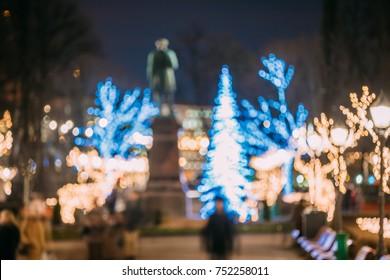 Helsinki, Finland. Defocused Blue Bokeh Background With Statue Of Johan Ludvig Runeberg On Esplanadi Park In Lighting At Evening Night Illumination. Landmark On A Winter Christmas Xmas Holiday Season