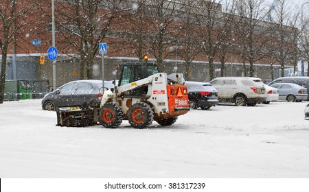 HELSINKI, FINLAND - JANUARY 10, 2016: Snow tractor removes snow during snowfall and blizzards in parking lot in Katajanokka