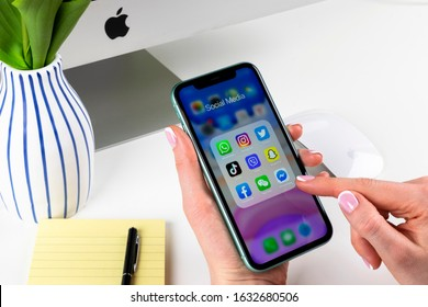 Helsinki, Finland, January 28, 2020: Apple iPhone 11 in woman hands with icons of social media facebook, instagram, twitter, snapchat application on screen. Social media icons. Social network