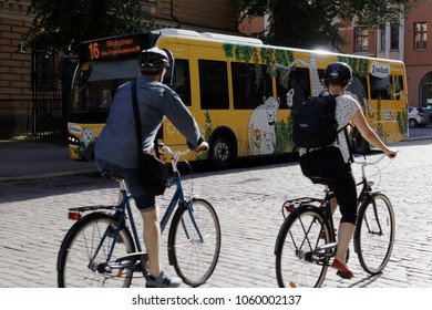 HELSINKI, FINLAND - JULY 15, 2017: People on bicycles against bus on line 16 moving to Helsinki Zoo. Located on Korkeasaari island, the zoo is one of the most popular places among visitors in Helsinki