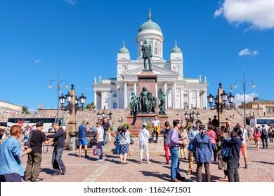 HELSINKI, FINLAND - JULY 19, 2016: Many tourists near statue of Alexander II on the Senate Square