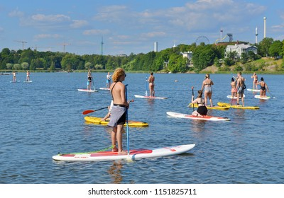 HELSINKI, FINLAND - JULY 19, 2018: Stand up paddle surfing and stand up paddle boarding (SUP), offshoot of surfing, in Toolonlahti bay. Sportsmen