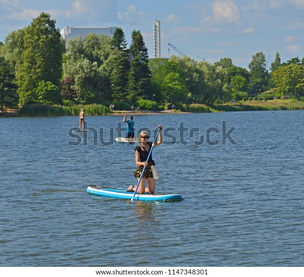 HELSINKI, FINLAND - JULY 19, 2018: Stand up paddle surfing and stand up paddle boarding (SUP), offshoot of surfing, in Toolonlahti bay. Water landscape