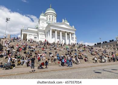 HELSINKI, FINLAND - JUNE 10, 2017: People sit on stair steps in front of St. Nicholas cathedral in Helsinki, Finland on June 10, 2017