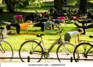 Helsinki, FINLAND - JUNE 12, 2018: Large group of people working out in public city Park in Helsinki. Sunny summer day, green lawn, men and women of all ages doing sports outdoors.