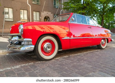 Helsinki, Finland - June 13, 2015: Old red Ford Custom Deluxe Tudor car is parked on the roadside. 1951 year modification with convertible roof