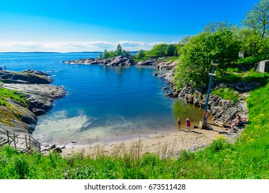 HELSINKI, FINLAND - JUNE 15, 2017: View of a bay and a beach in Suomenlinna Island, with bathers, in Helsinki, Finland