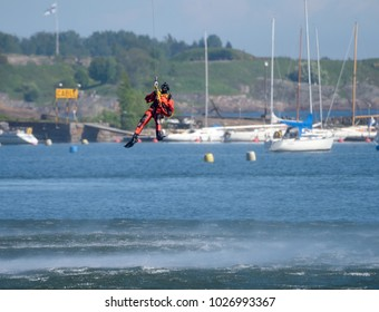 HELSINKI, FINLAND -June 9, 2017: Unidentified Finnish Coast Guard rescue swimmer drops down to the Baltic Sea be a wire in rescue performance in the Kaivopuisto Air Show 2017.