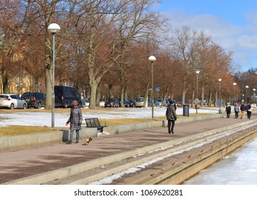 HELSINKI, FINLAND - MARCH 23, 2018: Walk with dog along embankment in early spring