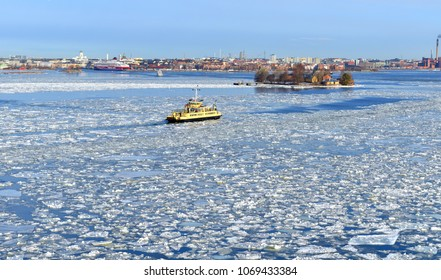 HELSINKI, FINLAND - MARCH 26, 2018: Service ferry M/S Ehrensvard departs from Katajanokka and arrives at service dock of Suomenlinna fortress. Spring, ice drift