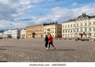 Helsinki, Finland - March 28, 2020: Citizens jogging at the empty Market Square due to the outbreak of the Coronavirus.