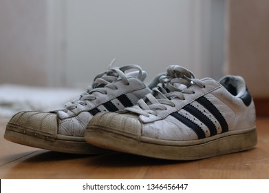 Helsinki, Finland - March 4th 2010: A pair of worn Adidas Superstar sneakers on a wooden apartment floor.