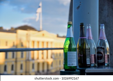 HELSINKI, FINLAND - MAY 1, 2017: Empty sparkling wine bottles on top of a trash bin outdoors at the Senate Square with the Finnish Government Palace and Finnish flag on the background at Mayday.