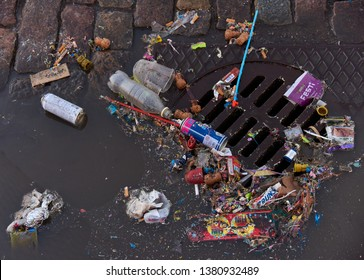 Helsinki, Finland - May 1, 2017: Plastic and other trash over sewer and partly floating in a puddle on cobble street after first of May celebrations.