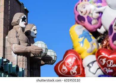 HELSINKI, FINLAND - MAY 1, 2017: Statues by the side of the Helsinki Central Railway Station  wearing rock band Kiss masks during First of May celebrations with colourful balloons on the foreground.