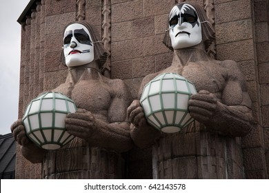 HELSINKI, FINLAND - MAY 1, 2017: Stone statues by the side of the Helsinki Central Railway Station wearing rock band Kiss masks during First of May celebrations.