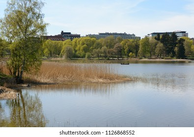 HELSINKI, FINLAND - May 13, 2018: People row a boat on Toolo bay in the City Park in Helsinki. Scandic Park and Crowne Plaza hotels can be seen above the trees.