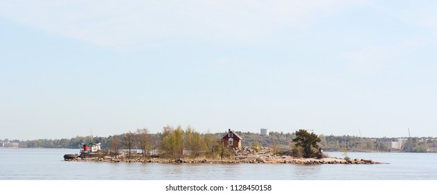 HELSINKI, FINLAND - May 14, 2018: Boat moored on Katajanokanluoto island with small dwellings visible through the trees - seen from the ferry between Helsinki and Suomenlinna