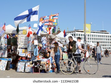 HELSINKI, FINLAND - May 14, 2018: Tourists peruse a stall laden with souvenirs and flags in Market Square, Helsinki