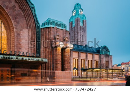 Helsinki, Finland. Night View Of Statues On Entrance To Helsinki Central Railway Station. Evening Or Night Illumination.