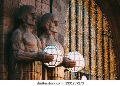 Helsinki, Finland. Night View Of Two Pairs Of Statues Holding The Spherical Lamps On Entrance To Helsinki Central Railway Station. Evening Or Night Illumination.