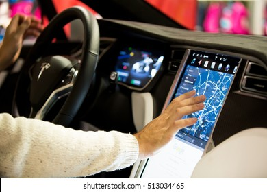 HELSINKI, FINLAND - NOVEMBER 04, 2016: The interior of a Tesla Model X electric car with large touch screen dashboard.  Hand using gps navigation system.