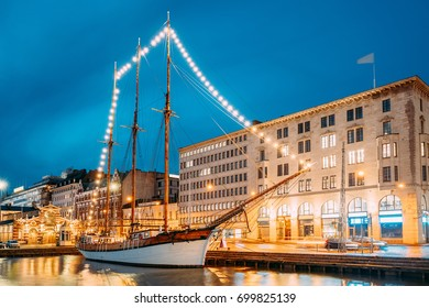 Helsinki, Finland. Old Wooden Sailing Vessel Ship Schooner Is Moored To The City Pier, Jetty. Unusual Cafe Restaurant In City Center In Lighting At Evening Or Night Illumination