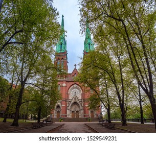 Helsinki. Finland. The road leads to the Church of St.John in Helsinki. Lutheran church. Religious building. Terracotta Cathedral with pointed spires. Gothic Cathedral on the background of green trees